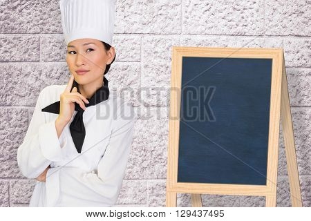 Portrait of thoughtful female cook in kitchen against image of a wall