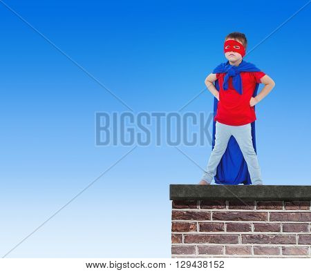 Masked boy pretending to be superhero against red brick wall
