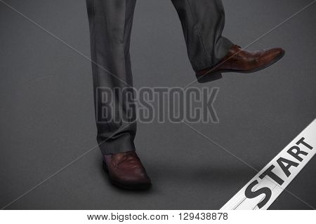Businessman stepping against grey