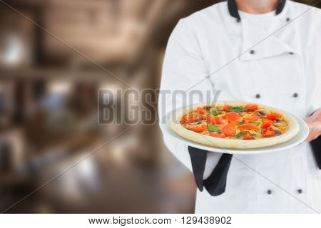 Male chef offering pizza against large vats of beer