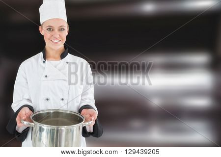 Happy female chef holding kitchen utensil against deep fat fryers