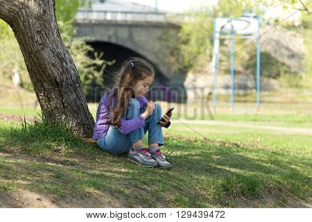 Cute little girl sitting on the grass in a park with a mobile phone in her hands and sending message on phone mobile