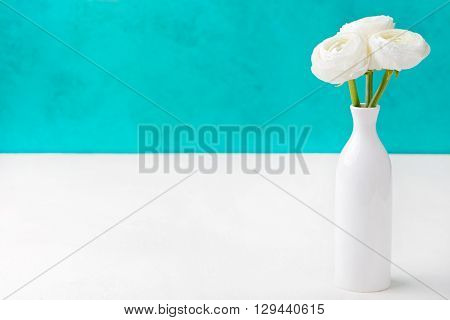 White ranunculus flowers in a ceramic vase Blue background Copy space