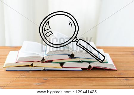 education, school, literature, reading and knowledge concept - close up of books on wooden table with magnifying glass doodle