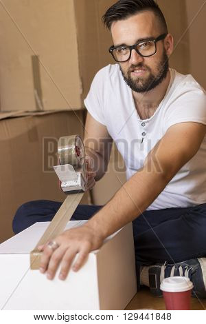 Young man packing things and taping boxes preparing for moving out the apartment