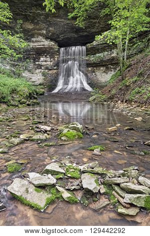 Water flows from Porter Cave and immediately tumbles over a steep waterfall in rural Indiana.