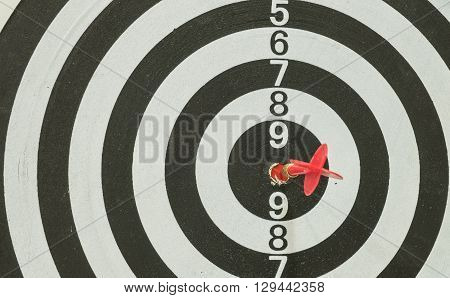 Red arrow at the center of dart board background