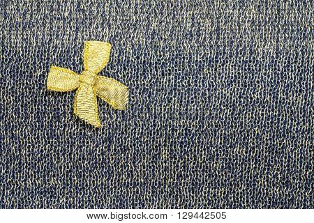 Gold ribbon on black fabric texture background