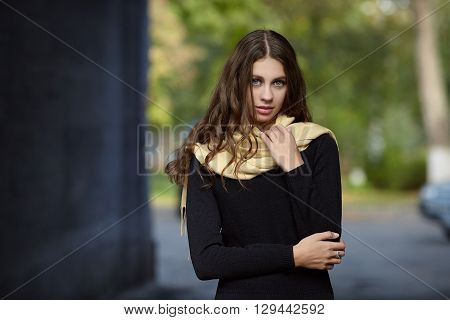 Young beautiful brunette woman with long wavy hair posing outdoors in black sweater and yellow scarf