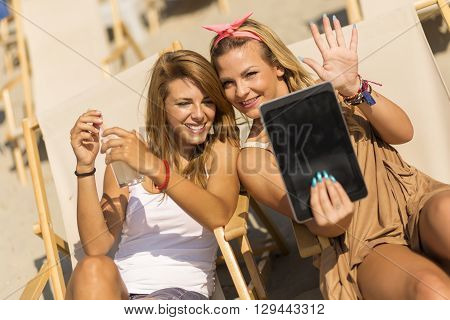 Two beautiful young girls lying on a sunbeds on the beach taking a selfie with a tablet computer
