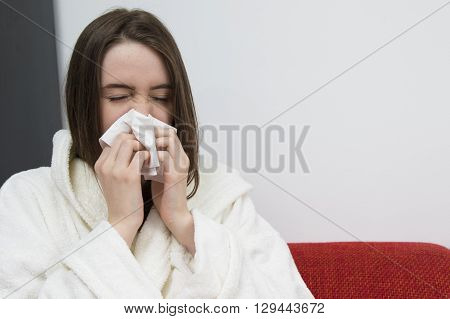 Sick young girl in white bathrobe is sneezing