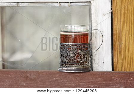 glass holder with glass of tea near window and wood wall