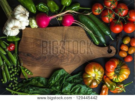 Fresh raw vegetable ingredients for healthy cooking or salad making with dark wooden cutting baoard in center, top view, copy space. Diet or vegetarian food concept, horizontal composition