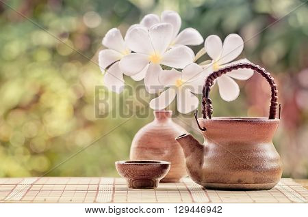 Soft focus and blurred teacup and teapot with vase of plumeria flower on nature background