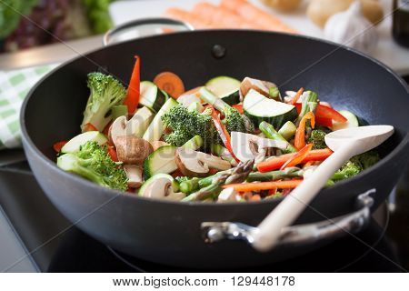 Wok stir fry vegetables with zucchini, spring asparagus, paprika, carrot and broccoli, closeup in a wok pan in a kitchen, selective focus