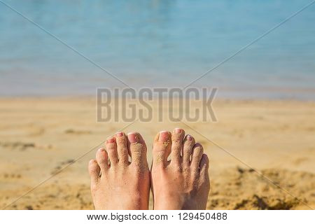 Women's feet in the sand against beach and sea background. Holiday concept