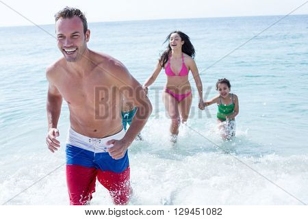 Father running against mother holding children on sea shore at beach