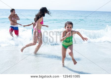 Girl running against family on sea shore at beach