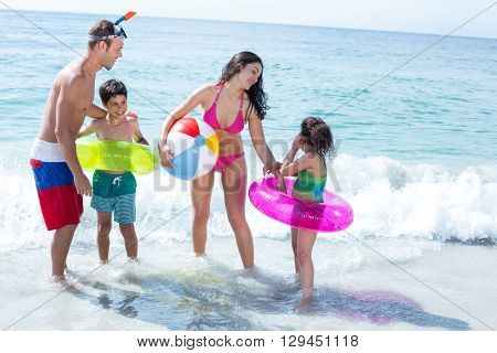 Mother and father with son looking at girl standing on sea shore