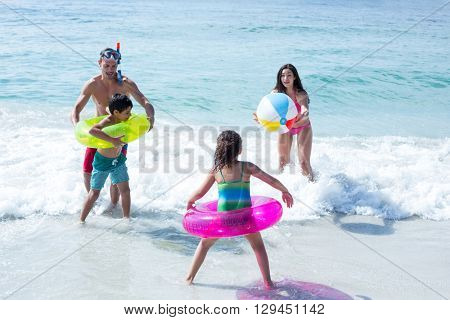 Happy family playing with beach ball on sea shore at beach