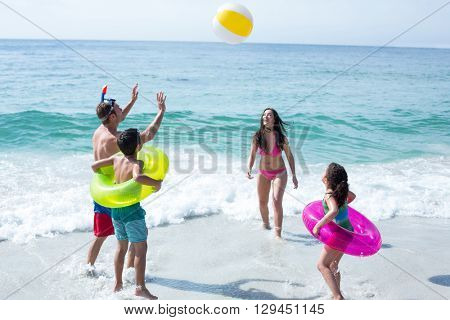Happy family enjoying with beach ball on sea shore at beach