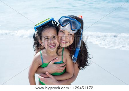 Portrait of mother with daughter wearing diving goggles at beach
