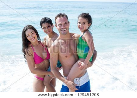 Portrait of smiling parents with children standing on sea shore at beach