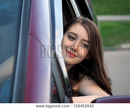 Young, beautiful girl at the wheel of the car. The girl looks in the rearview mirror and smiles. The girl has freckles. woman driver