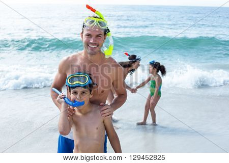 Family wearing diving goggles standing on sea shore at beach