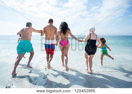Rear view of multi generation family walking towards sea