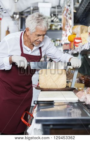 Salesman Slicing Cheese With Knife In Shop