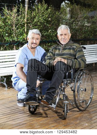 Physiotherapist Crouching By Senior Man In Wheelchair At Lawn