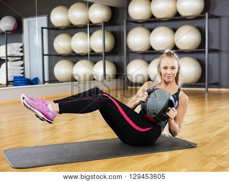 Confident Young Woman Exercising With Medicine Ball In Gym