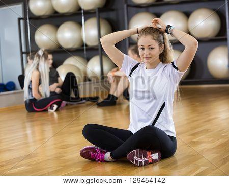 Fit Woman Tying Hair On Hardwood Floor In Gym
