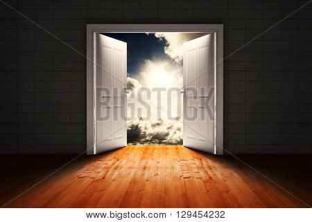 Door opening in dark room to show sky against dark sky with white clouds