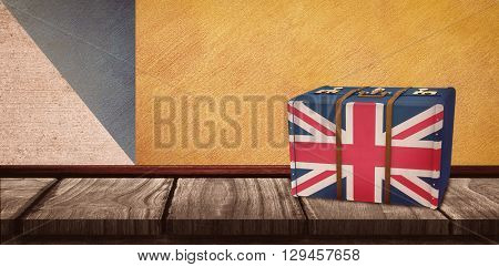 Great Britain flag suitcase against wooden table on a texture and coloured wall