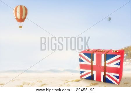 Great Britain flag suitcase against beautiful beach and blue sky