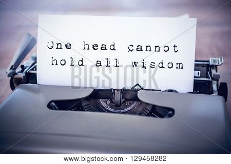 The sentence one head cannot hold all wisdom against white background against a paper in a printer
