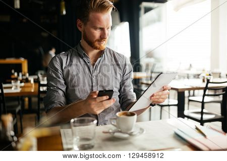 Handsome young businessman constantly busy and working