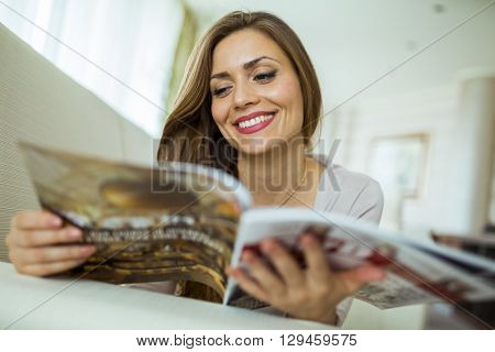 Beautiful woman on a sofa reading a paper in a well lit stylish living room