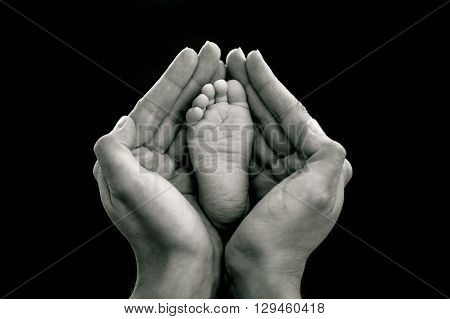Black and White mother's hands holding baby foot