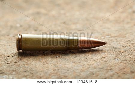 Close-up of kalashnikov bullet on rusted iron plate