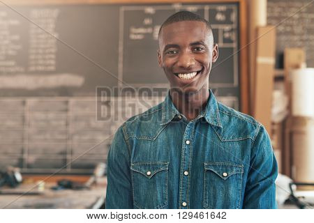 Portrait of a young African designer standing in his workshop studio, smiling handsomely at the camera