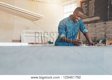 Low angle view of a handsome young designer of African descent, working with pen and paper at a large work table in his stduio
