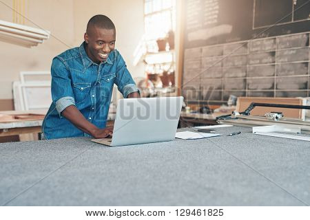 Smiling man of African descent working on his laptop on a large work table in his workshop, from where he runs his small business