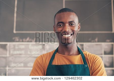 Head and shoulders portrait of a handsome African man wearing an apron and smiling broadly at the camera, while standing in the workshop where he works as an artisan