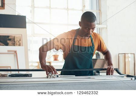 Young African artisan concentrating carefully while using a work tool with skill and expertise in a picture framing workshop