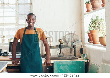 Portrait of a young African artisan standing in his beautifully lit workshop studio, leaning on his desk and smiling confidently at the camera