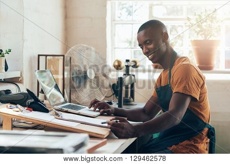 Handsome craftsman and small business owner fo African descent, sitting at the desk in his workshop studio, using his laptop to process some paperwork and smiling happily