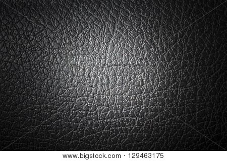 Black and grainy texture of synthetic skin with center soft light.